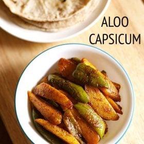 top shot of aloo capsicum or aloo shimla mirch ki sabji in a white green rimmed bowl on a beige colored wooden board