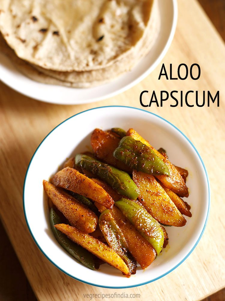 top shot of aloo capsicum or aloo shimla mirch ki sabji in a white green rimmed bowl on a beige colored wooden board