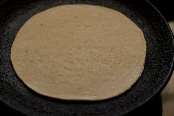 frying aloo paratha on skillet