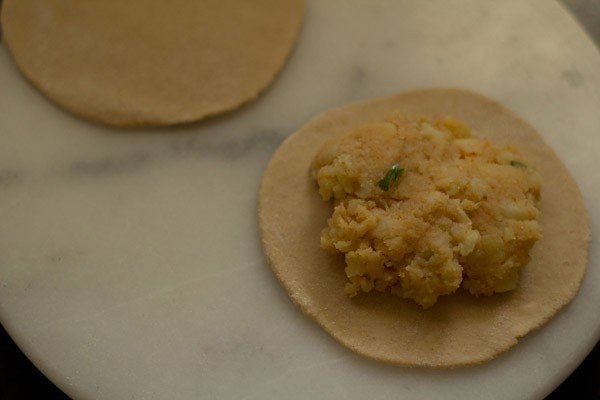placing aloo stuffing on rolled paratha
