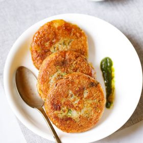 Three aloo tikki kept vertically on a white plate with a spoon and a splash of cilantro dip on the plate placed on a light grey fabric