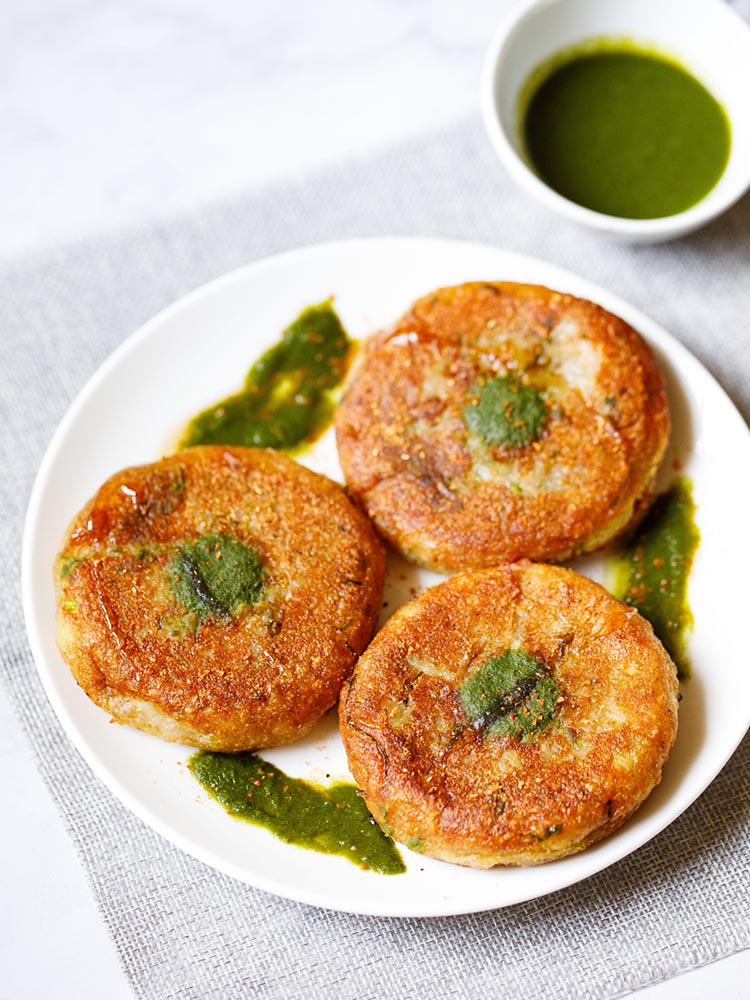Three aloo tikki on a white plate kept in a triangular position dotted with cilantro dip on the top of the tikki with a splash of cilantro dip around.