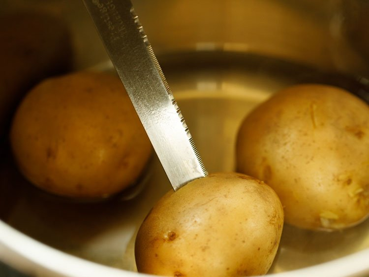 checking the doneness of potatoes with a knife