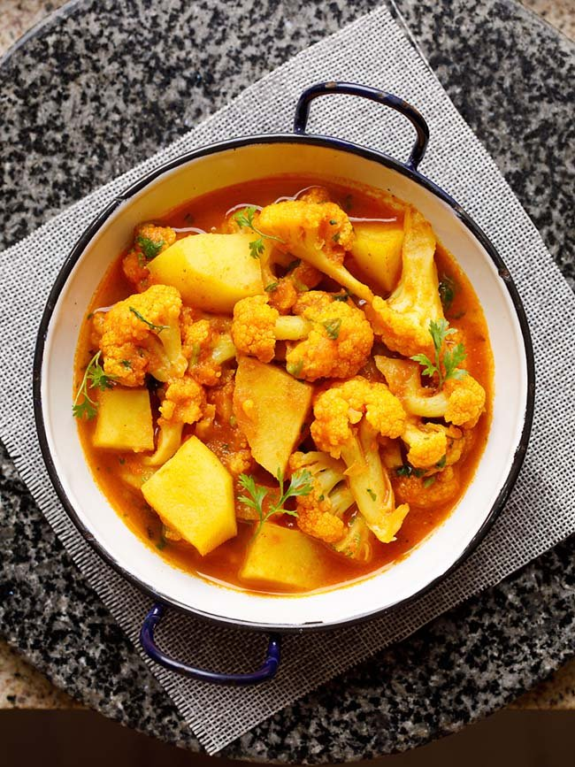 instant pot aloo gobi served in a small white wok on a grey jute mat