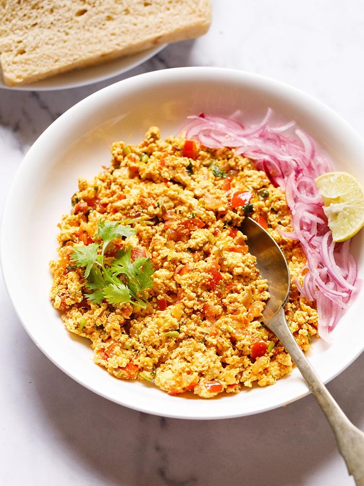 Paneer Bhurji served in a shallow white bowl garnished with one coriander sprig with a spoon inside the bhurji and topped with some sliced onions and a wedge of lemon