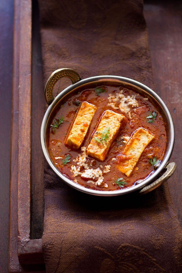 kadai paneer recipe gravy in a small copper kadai garnished with coriander sprigs and grated paneer