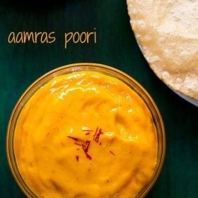 top shot of aamras in glass bowl with a few saffron strands on top with a side of poori on a green wooden board with a text layover