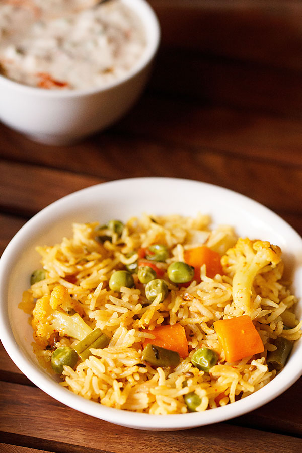 instant pot veg pulao served in a white bowl on a wooden tray