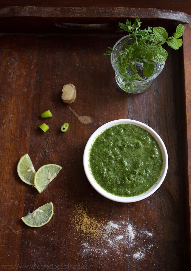 cilantro mint chutney in white bowl on a wooden board with slices of lemon, chopped green chillies and ginger and sprinkled salt and cumin powder on a wooden board