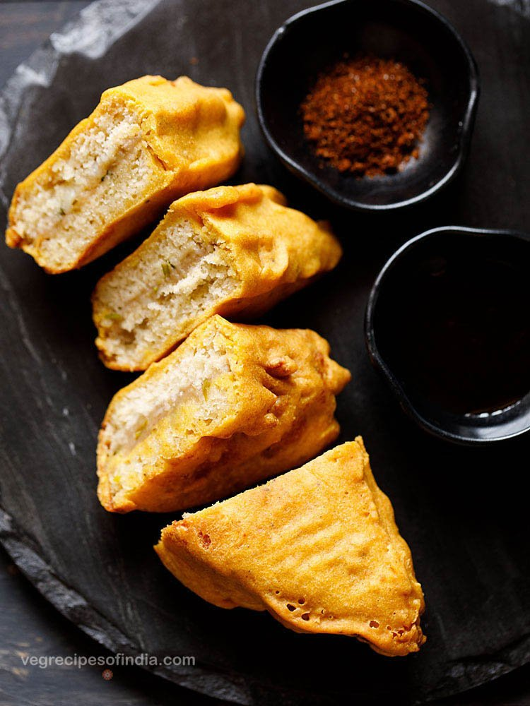stuffed bread pakoda slices on a black slate board with two black small bowl of dry garlic chutney and tamarind chutney