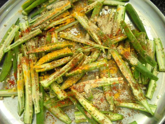 sprinkling spice powders on bhindi or okra