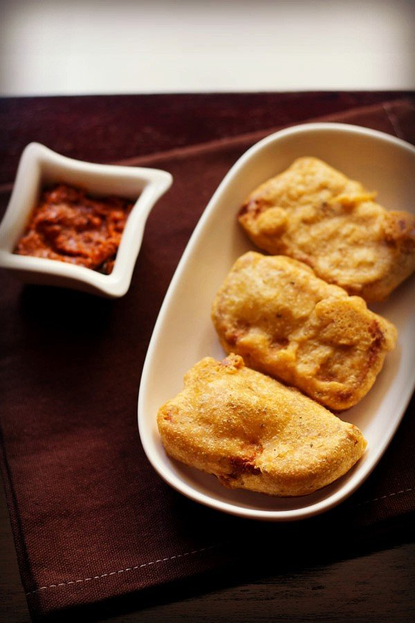 bread bajji in an oval white plate with a side of tomato chutney on a dark brown napkin