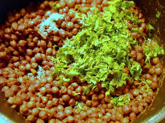 adding coriander leaves to kala chana