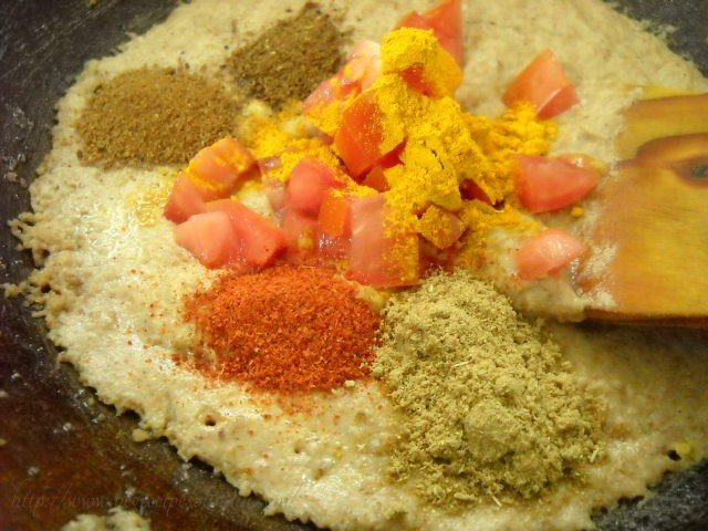 adding tomatoes spices to bharli vangi masala