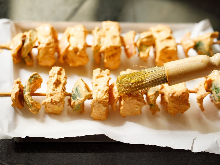brushing oil on the paneer cubes, onions and capsicum
