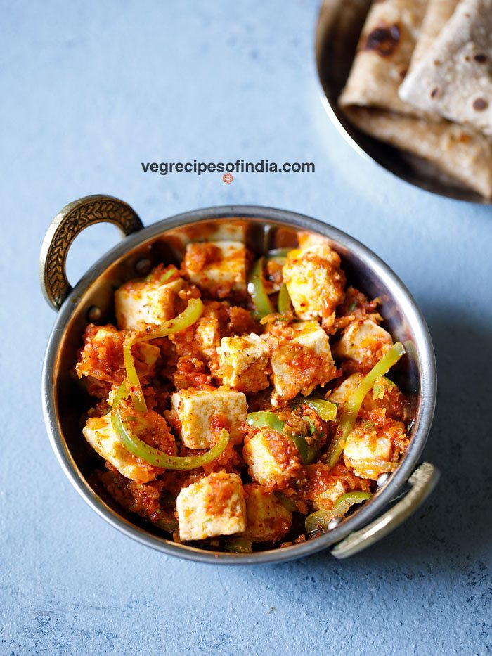 kadai paneer in a small kadai (Indian wok) on a light blue board