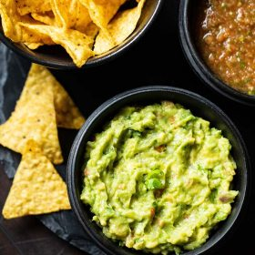 guacamole served in a black wooden bowl with a side black bowl of nachos and tomato salsa