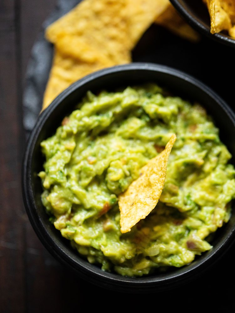 nacho dipped in guacamole dip in a wooden black bowl on a round black granite board