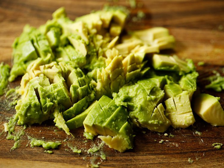 chopped avocado on a wooden chopping board