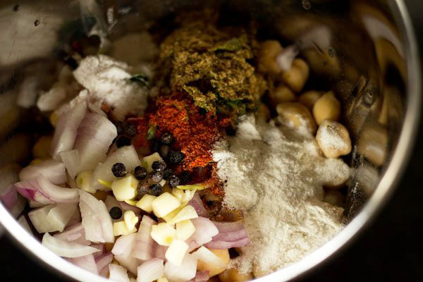 spices and herbs added to soaked chickpeas in the grinder jar