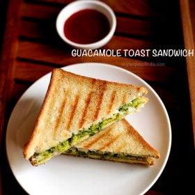 एवोकाडो सैंडविच को एक प्लेट में टोमैटो सॉस के साथ परोसा जाता है