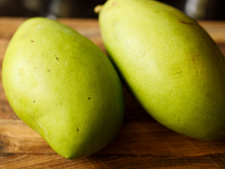 unripe green mangoes on chopping board