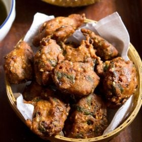 palak pakoda served in a bowl on a wooden board