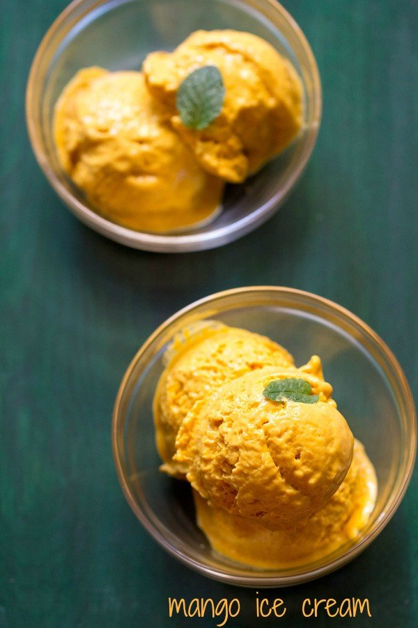 scoops of mango ice cream in two glass bowls garnished with a mint leaf on a green board