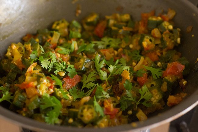garnishing bhindi ki sabji with coriander leaves