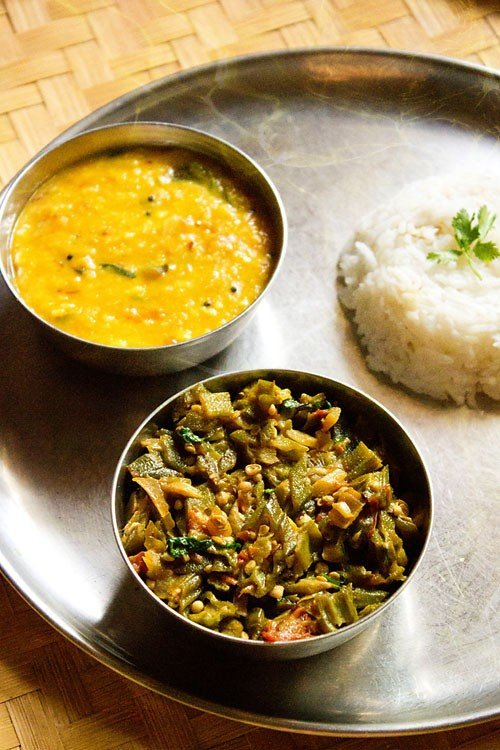 bhindi ki sabji served with dal and steamed rice in steel bowls