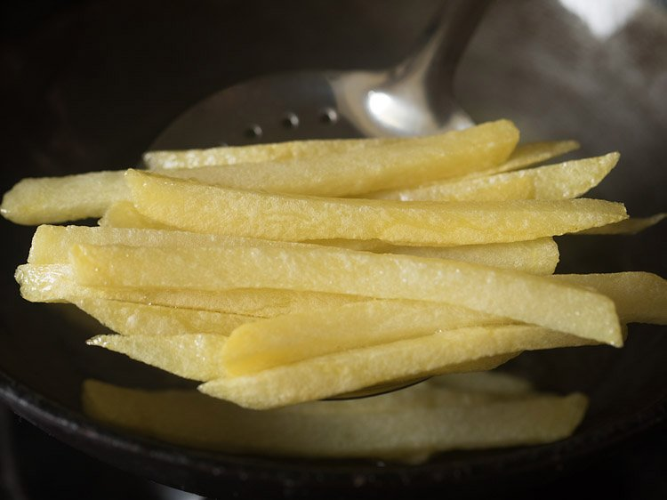 first fry french fries being removed from oil to drain