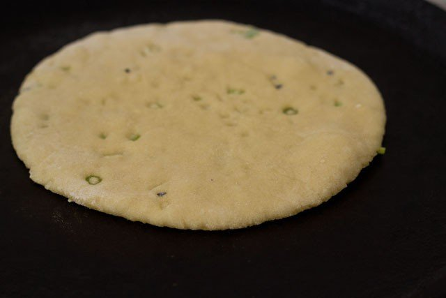 placing garlic naan on tava