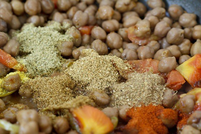 adding spices to amritsari chole recipe