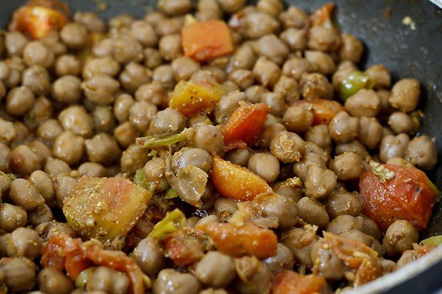 stir the spices for making amritsari chole recipe