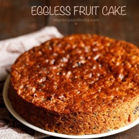 eggless fruit cake placed on a white plate with a printed napkin at the side