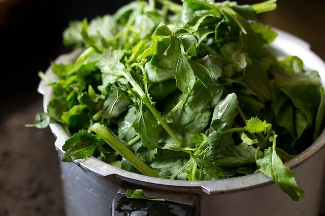 adding greens in pressure cooker for sarson ka saag recipe