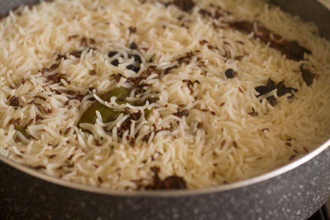 preparing jeera rice recipe
