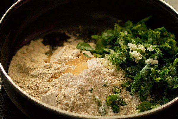 whole wheat flour, salt, methi leaves, green chilies, chopped garlic and oil in a bowl.