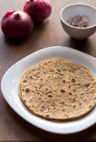two onion paratha stacked in a square white plate with red onions and chopped onions, green chillies in a small white bowl in background