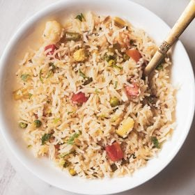 pulao served in a white shallow bowl with a brass serving spoon in the pulao
