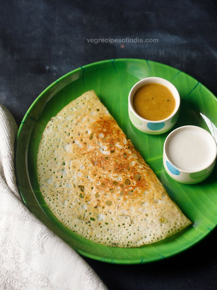 sooji dosa served in a green plate with a side of two bowls having sambar and coconut chutney on a dark black-blue board