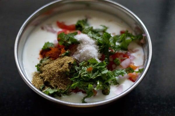 adding spices to onion tomato raita recipe