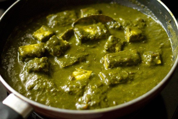 mixing cream in the palak paneer gravy