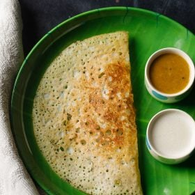 rava dosa served in a green plate with a side of two bowls having sambar and coconut chutney on a dark black-blue board