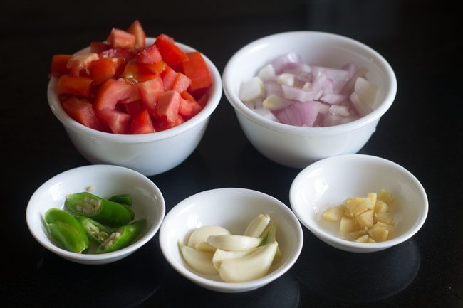 prepped up ingredients in white bowls - chopped onions, tomatoes, green chillies, garlic and ginger