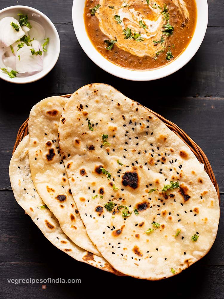 naan kept on top of each other in a cane basket. served with dal makhani in a white bowl and side of sliced onions garnished with coriander leaves in a small bowl.