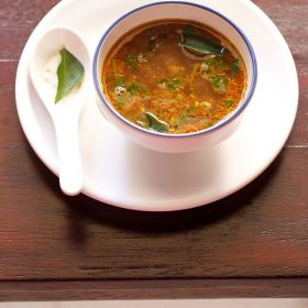 tamarind rasam served in a bowl on a white tray