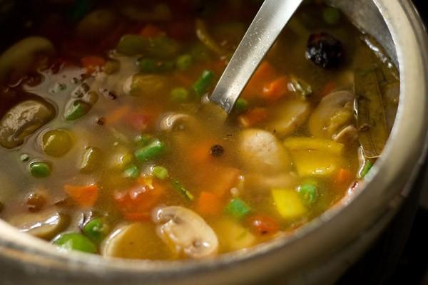 stir the vegetable pulao in pressure cooker, making veg pulav recipe