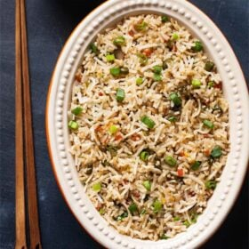 fried rice in an oval ceramic bowl with wooden chopsticks on a slate black board