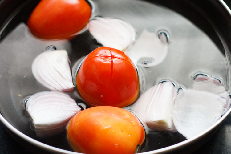 onions and tomatoes being blanched in hot water
